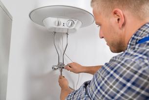 Plumber Repairing Electric Boilerの写真素材 [FYI00663177]