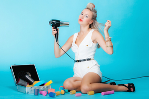 sexy girl retro styles in curlers with a hairdryer styling hairの写真素材 [FYI00663266]
