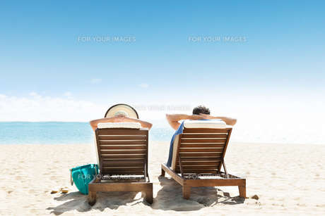 Couple relaxing on deck chairs at beach resortの写真素材 [FYI00663278]