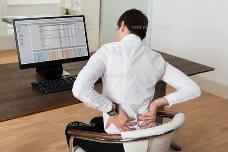 Businessman Suffering From Backache At Deskの写真素材 [FYI00663291]
