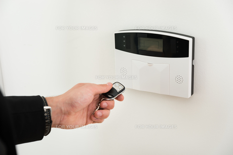 Hands With Remote Control In Front Of Security Systemの写真素材 [FYI00663293]