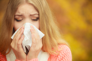 sick ill woman in autumn park sneezing in tissue.の素材 [FYI00663311]