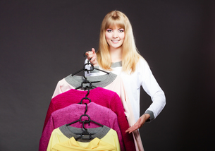 customer woman holding hangers with clothesの写真素材 [FYI00663328]