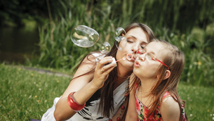 mother and little girl blowing soap bubbles in the park.の写真素材 [FYI00663347]