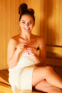 woman relaxing in a sauna room blowing soap bubblesの写真素材 [FYI00663358]