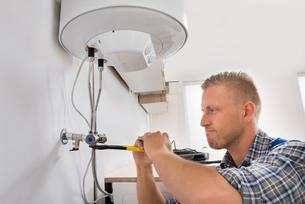 Repairman Repairing Electric Boilerの写真素材 [FYI00663392]