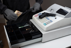 Robber Taking Money From Cash Registerの写真素材 [FYI00663398]
