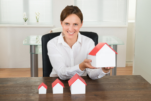 Businesswoman With House Models On Deskの写真素材 [FYI00663399]