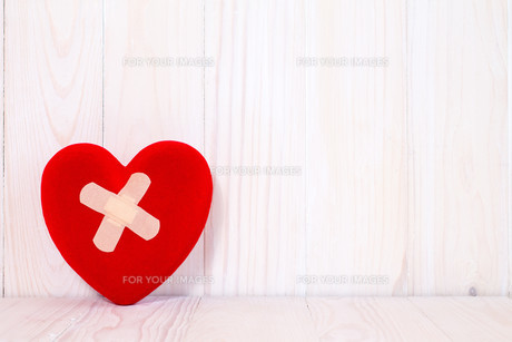 Injured heart  on the white wooden backgroundの素材 [FYI00663651]