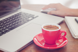 Red coffee cup with notepad and laptopの写真素材 [FYI00663653]