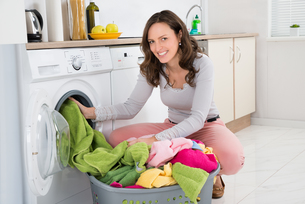 Woman Putting Clothes Into Washing Machineの写真素材 [FYI00663706]