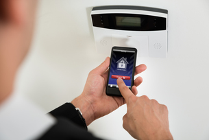 Businessperson Disarming Security System With Mobile Phoneの写真素材 [FYI00663710]