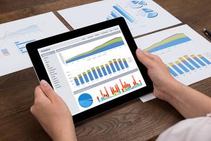 Person Analyzing Financial Statistics On Digital Tabletの写真素材 [FYI00663717]
