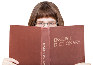 girl with spectacles looks over English Dictionaryの素材 [FYI00663790]