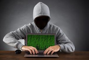 Man Hacking Laptop At Deskの写真素材 [FYI00663847]