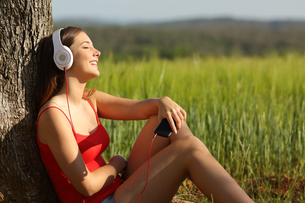 Girl listening to the music relaxed in a green fieldの写真素材 [FYI00663944]