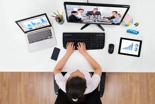 Businesswoman Videoconferencing With Co-workers On Computersの写真素材 [FYI00663986]
