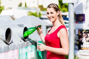 Frau auf Entsorgungshof wirft Flaschen in Containerの素材 [FYI00663988]