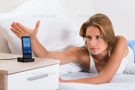 Woman Snoozing Alarm On Mobile Phoneの写真素材 [FYI00664104]