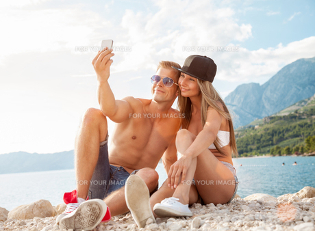 Couple sitting on a beach and taking a selfieの写真素材 [FYI00664158]