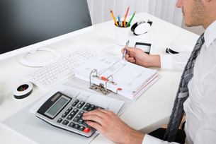 Businessperson Calculating Budget At Deskの写真素材 [FYI00664185]