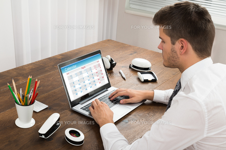 Businessman Looking At Calendar On Laptop In Officeの写真素材 [FYI00664190]