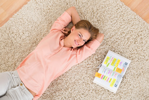 Woman With Diary Lying On Carpetの写真素材 [FYI00664265]