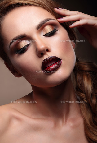 Closeup portrait of beautiful  stylish young woman model with bright makeup, with vinous lips. Makeup Face.  Beautiful Professional Holiday Make-up.の写真素材 [FYI00664282]