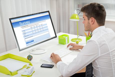 Businessman Filling Online Survey Form On Computerの写真素材 [FYI00664367]