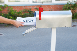 Person Hands Opening Mailbox To Remove Newspaperの素材 [FYI00664369]