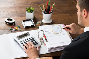 Businessman Inspecting Invoice At Deskの写真素材 [FYI00664378]