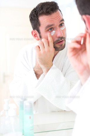 Young attractive man applying anti dark circles cream around eyesの素材 [FYI00664417]