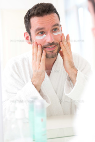 Young attractive man applying anti dark circles cream around eyesの素材 [FYI00664418]