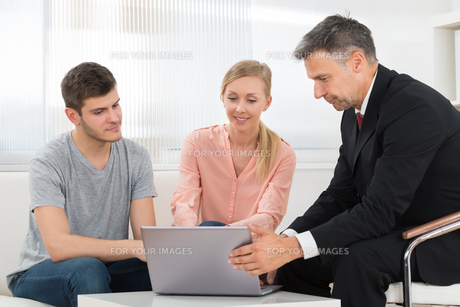 Consultant Explaining Investment Plan To Coupleの写真素材 [FYI00664510]