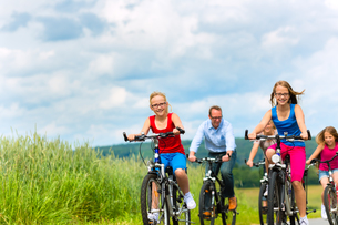 family riding bikes in the summer in village landscapeの写真素材 [FYI00666229]