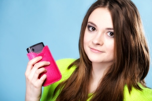 happy girl with mobile phone in pink coverの写真素材 [FYI00666946]