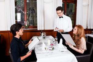 woman and man having dinner in restaurantの写真素材 [FYI00667632]