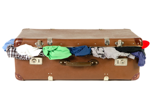 old suitcase full of clothes in front of a white backgroundの写真素材 [FYI00669089]