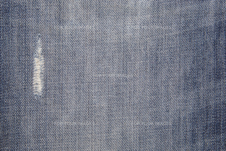 the worn blue jeans and textile backgroundの写真素材 [FYI00671025]