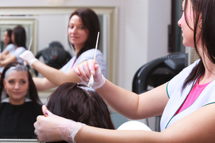 woman dying hair in hairdressing beauty salon. by hairstylist.の写真素材 [FYI00671352]