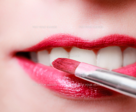 closeup of a female red pink lipstick lips with makeup brushの写真素材 [FYI00671405]