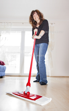 young woman doing fr?hjarhsputz and mopping the floorの素材 [FYI00671628]