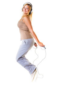 sports fitness girl with headphoes doing exercise with jump rope skipの写真素材 [FYI00672555]