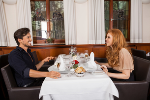 laughing couple having dinner in the restaurant at the tableの写真素材 [FYI00673081]