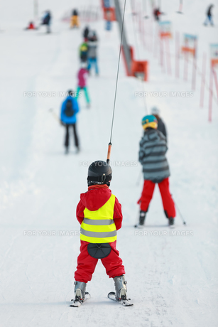child with red ski suit on surface liftの素材 [FYI00673664]