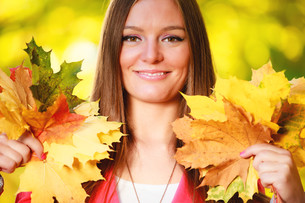 fall season. portrait girl woman holding autumnal leaves in the parkの写真素材 [FYI00674598]