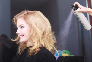 hairstylist with hairspray and female client blond girl in salonの写真素材 [FYI00674675]