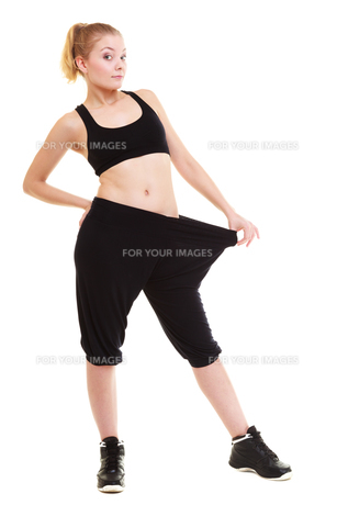happy woman showing how much weight she lost,big pantsの写真素材 [FYI00675526]
