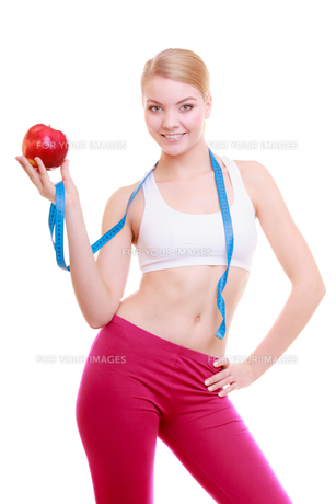diet. fitness woman fit girl with measure tape and apple fruitの写真素材 [FYI00675535]
