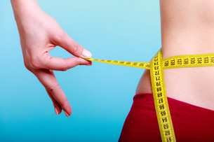 diet. fitness woman fit girl with measure tape measuring her waistの写真素材 [FYI00675537]